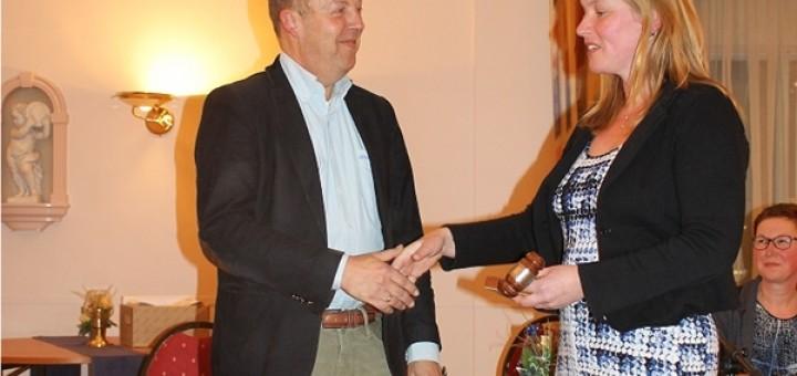 Ilja Bakker overhandigt de voorzittershamer aan Henri van Woerkom. Op de achtergrond Netty Hendriks.