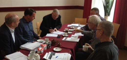 Pastoor Van der Mee plaatst zijn handtekening.