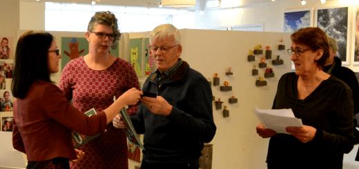 Ben van der Wal krijgt de prijs uit handen van Marianne Scalf van het Team KunstSuper . 'Mede-teamleden' Ina Hoeneveld en Teuni Vogelaar kijken toe.