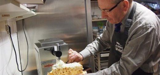 Oud-burgemeester John de Prieëlle van Ouderkerk stak in 2013 de handen uit de mouwen in de Gouderakse Bakkerswinkel tijdens de vrijwilligersactie NLDoet.