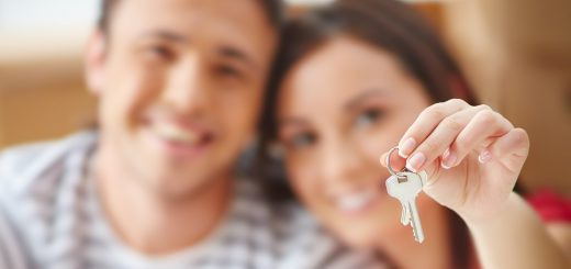 Hand of young woman showing key from new flat