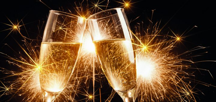 Glasses of champagne and sparklers on bright background with sparklers