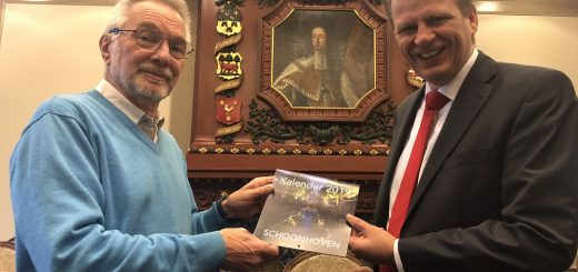 Fotograaf Rob Glastra (links) overhandigt het eerste exemplaar van de Schoonhoven Kalender 2019 officieel aan wethouder Jan Vente.