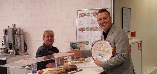 Aan Comenius Krimpen is de gouden Gezonde Schoolkantine-schaal 2018 toegekend voor het gezonde aanbod aan broodjes, groente, fruit en water. Directeur Mark Tange (rechts) reikt de trofee uit aan cateringmedewerkster Carla. (Foto: PR Comenius College)