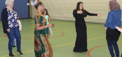Workshop dansen, waarbij vrouwen met verschillende nationaliteiten samen dansen.